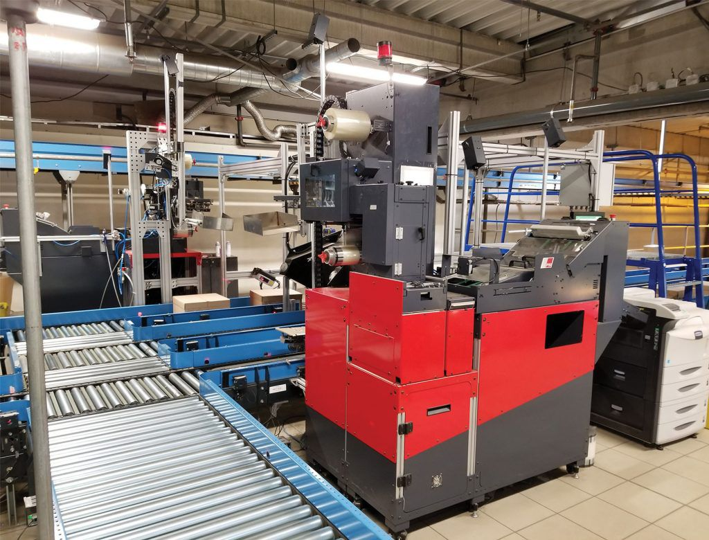 PSI Engineering Autoslip automated packing slip with top or side application shown on order fulfillment conveyor line