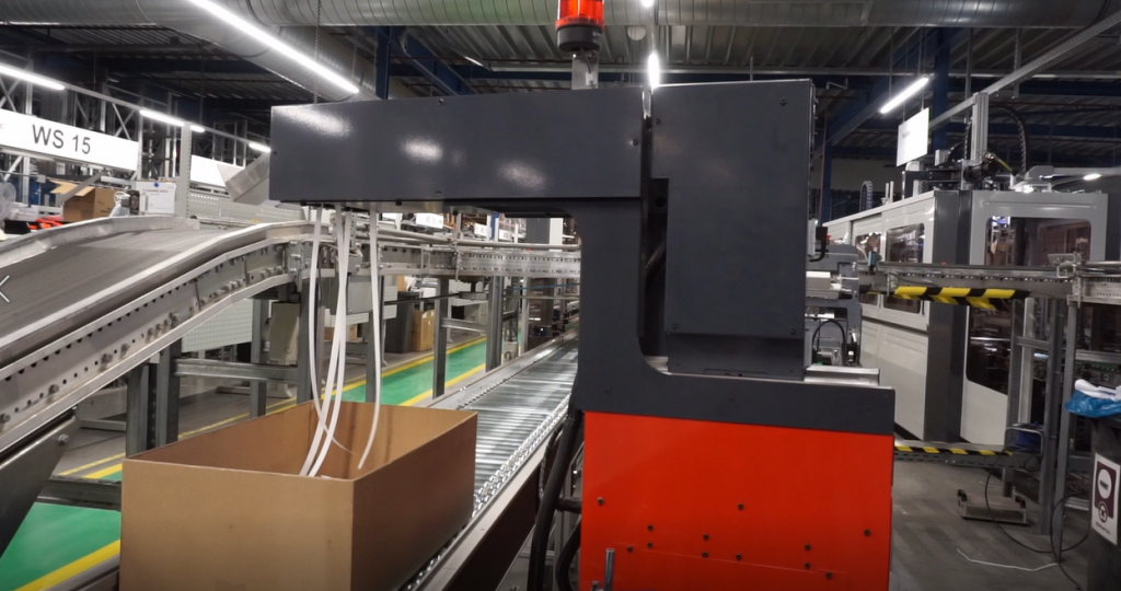 Print Feeder inserting a document into a box on a conveyor in a warehouse